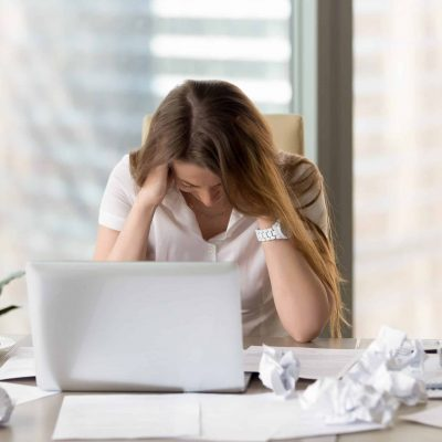 Desperate businesswoman sitting at the desk with laptop and crumpled paper. Female office worker suffers because of too much mess in her thoughts. Stressed woman entrepreneur feeling creativity crisis